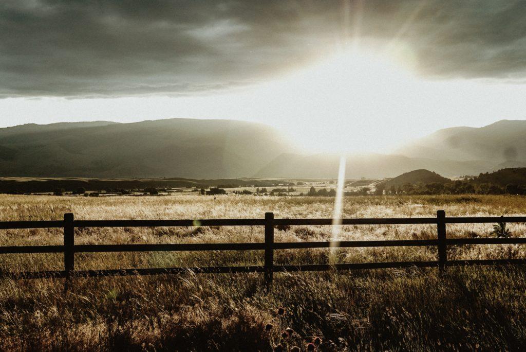 light beam through clouds, over a field